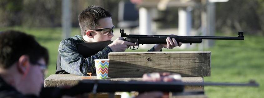 Adolescente disparando un rifle